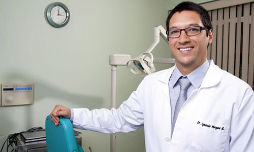 Picture of a smiling Premier Holistic Dental dentist in San José, Costa Rica.  The dentist is wearing a white coat and his arm Is resting on a modern dentist chair.