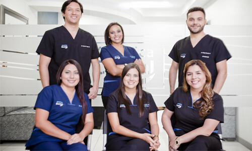Picture of a smiling group of Premier Holistic dentists and assistants in San José, Costa Rica.  Three are standing in the back and three are sitting in front of them.