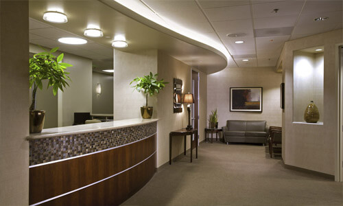 Picture of a dental office reception area.  The picture shows warm beige colors and a well-lighted plush interior.