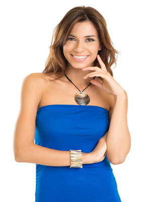 Picture of a beautiful woman wearing a blue dress and  showing her happiness with the holistic dental procedure she had at Premier Holistic Dental in San José, Costa Rica